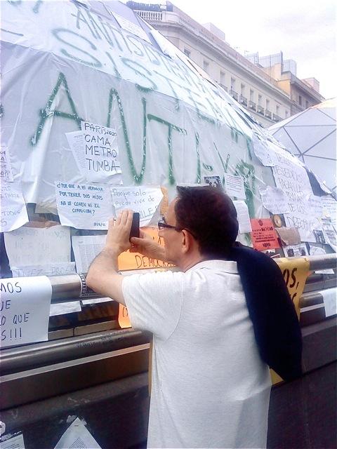 Mucha gente fotografía la Gran Concha de Esperanza Aguirre que cubre la boca del metro y que está empapelada de ocurrencias.